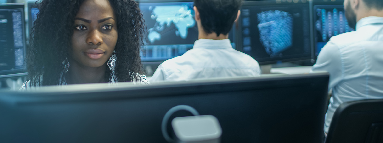 Image d'une femme et de deux hommes travaillant dans une installation informatique surveillant les informations dans un environnement sécurisé.