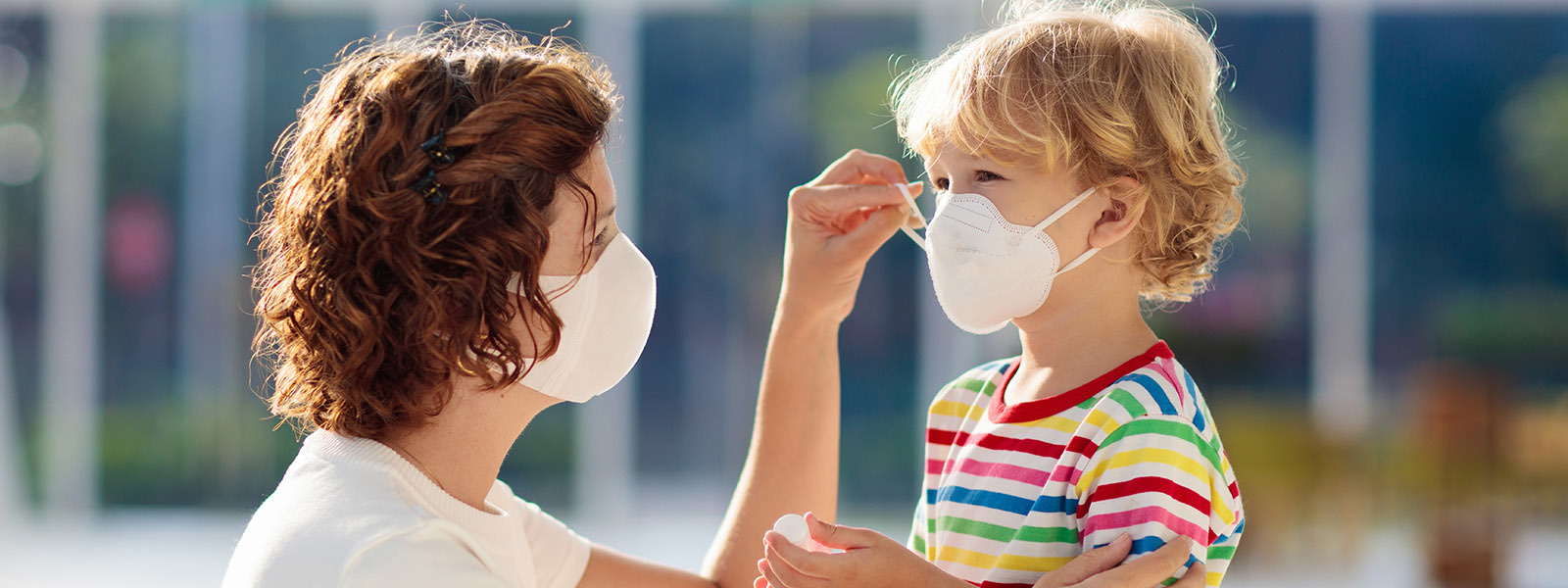 Image of a mother putting a mask on her child.