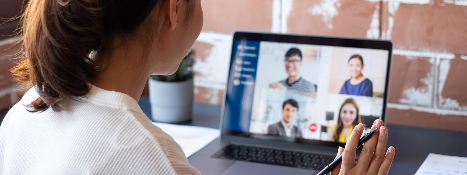 Image d'une femme ayant un appel vidéo en ligne avec des collègues.