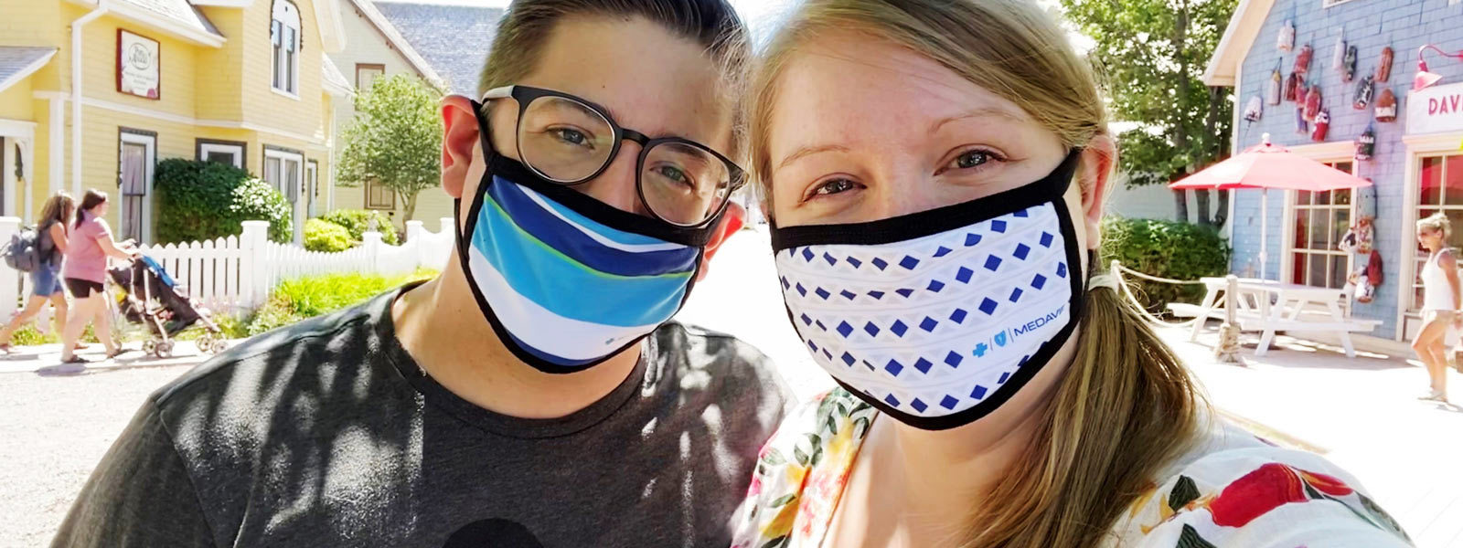 Image of a man and woman wearing masks on a small town main street