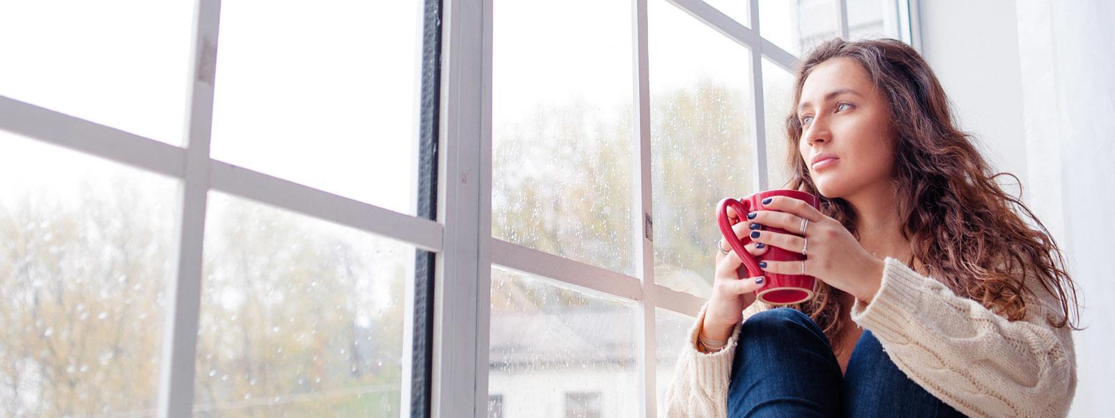 Image d'une femme assise à la fenêtre en tenant une tasse