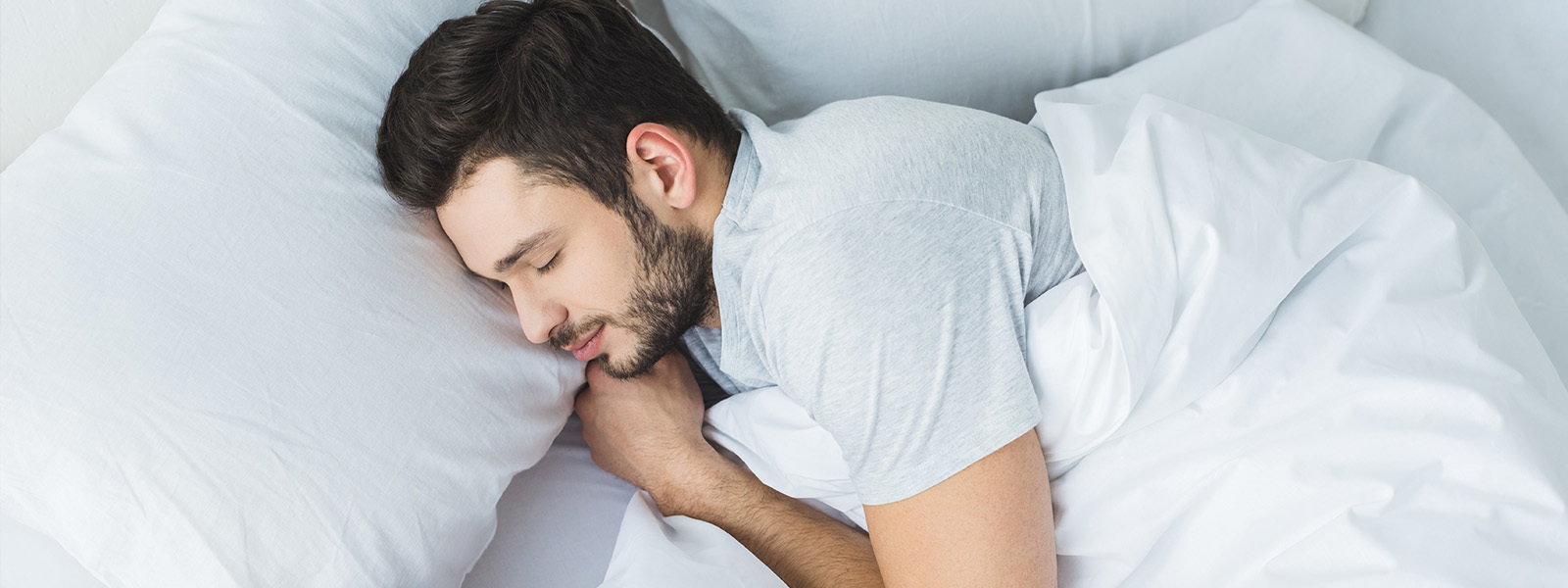 Image of a man sleeping in bed, getting a good night sleep.