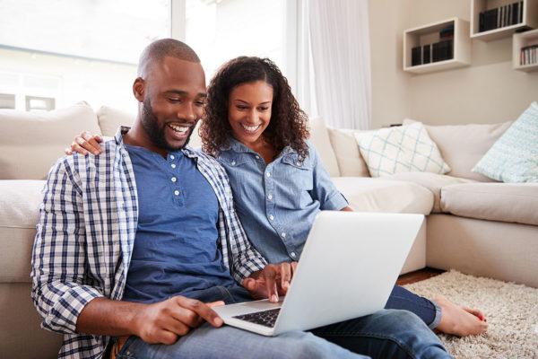 Un couple assis sur un canapé effectue des recherches sur les Garanties facultatives