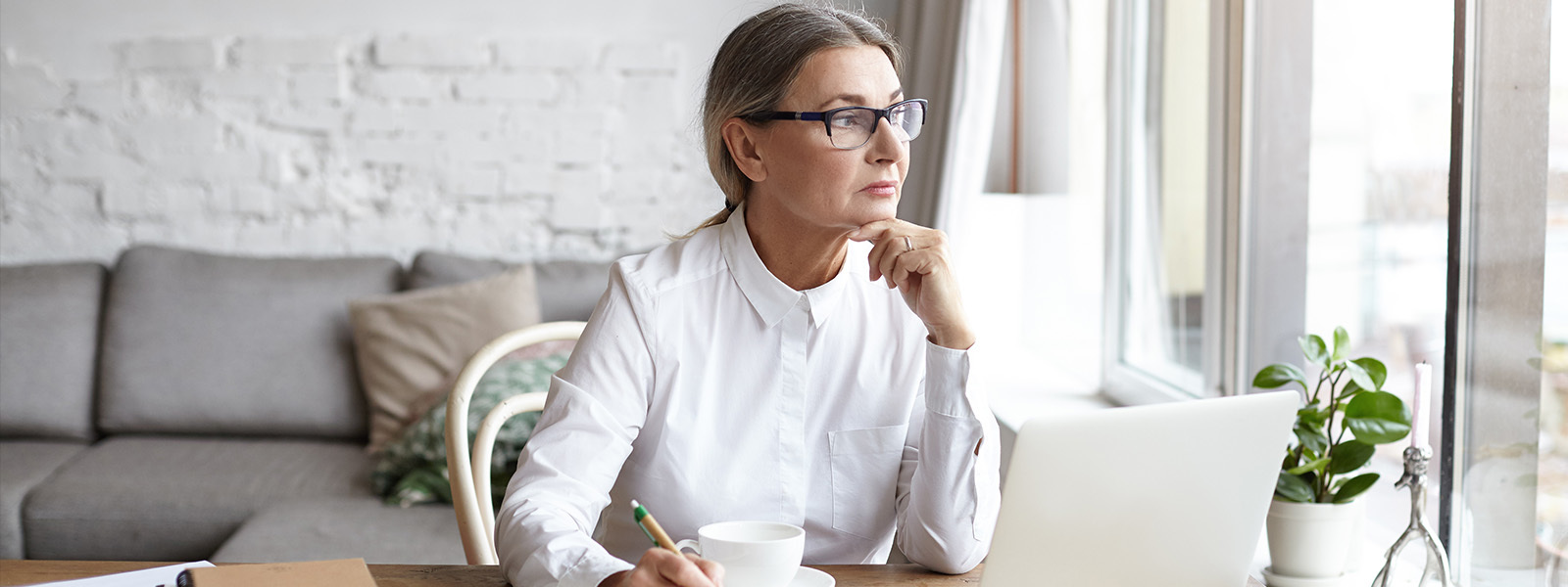 Image of mature woman in thought while working on laptop