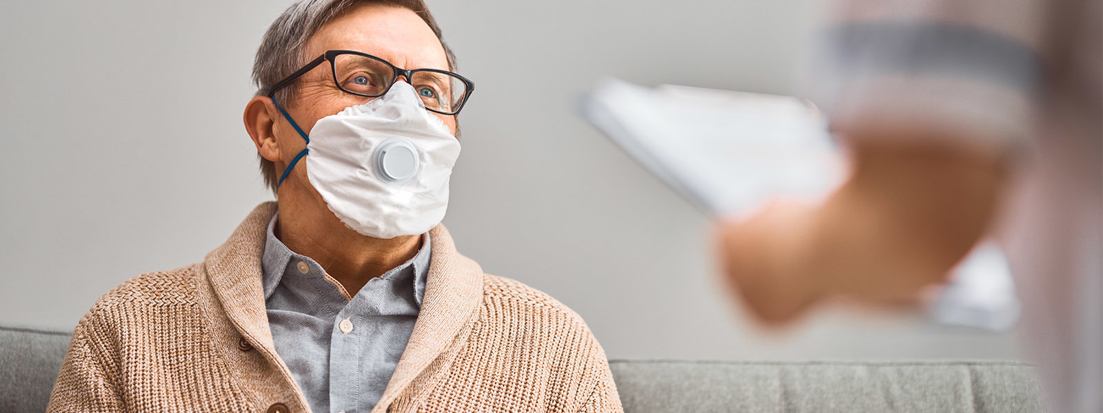Elderly Male Wearing Face Mask While Talking To Doctor