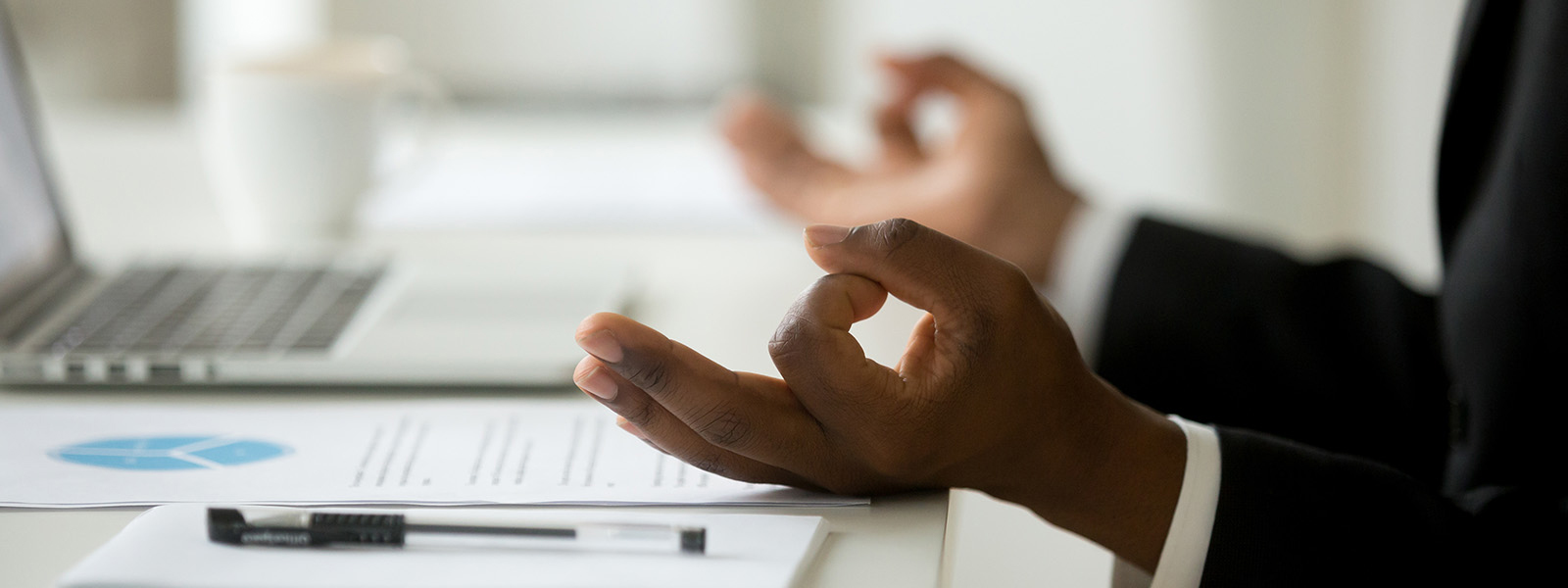 Image of hands meditating while working from desk
