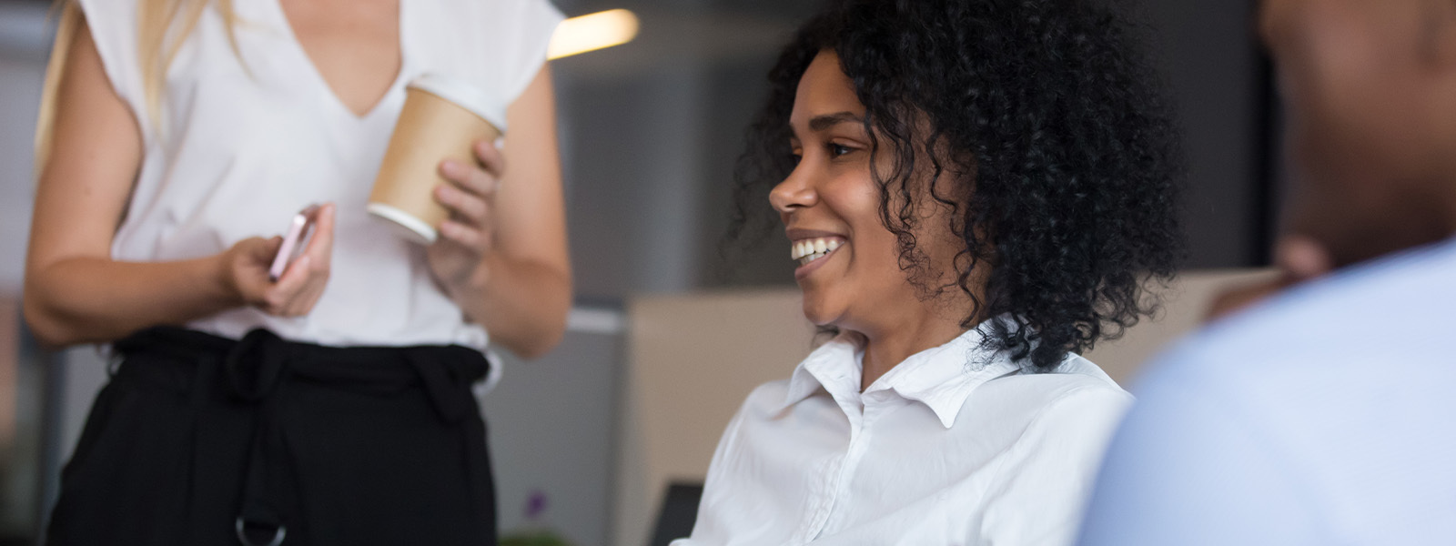 Image Of Woman In Office Setting Talking With Coworkers