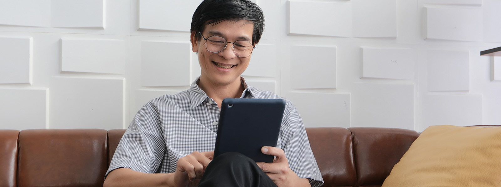 Image Of Man Smiling While Video Calling On Tablet Sitting On Couch