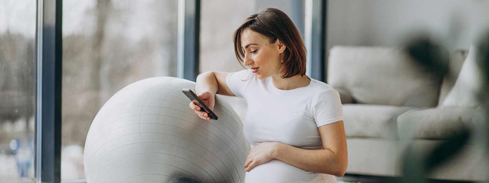 Pregnant Woman On Smartphone For Virtual Physio