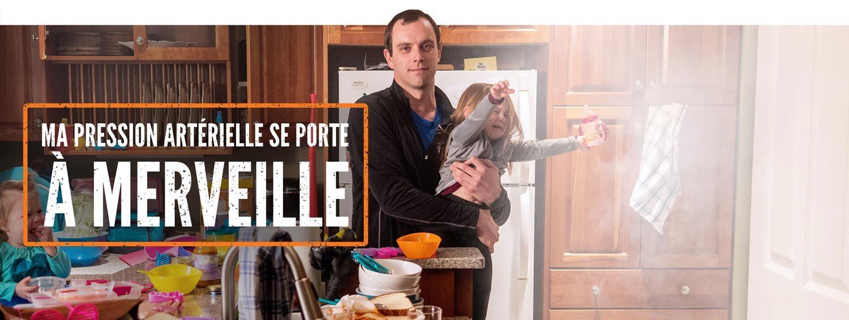 Photo d'un père qui porte un enfant qui pleure au milieu d'une cuisine. Le texte « Ma pression artérielle se porte à merveille » accompagne la photo.