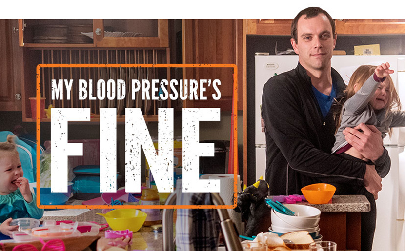 "Photo of a father in a kitchen holding a crying child. Caption reads: ""My blood pressure's fine."""